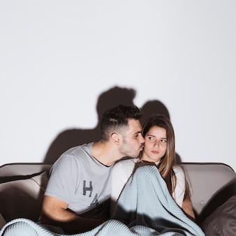 Junger kerl, der die verärgerte dame auf sofa fernsieht küsst