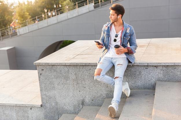 Junger kerl, der draußen mit dem handy geht, kaffee trinkt und musik hört