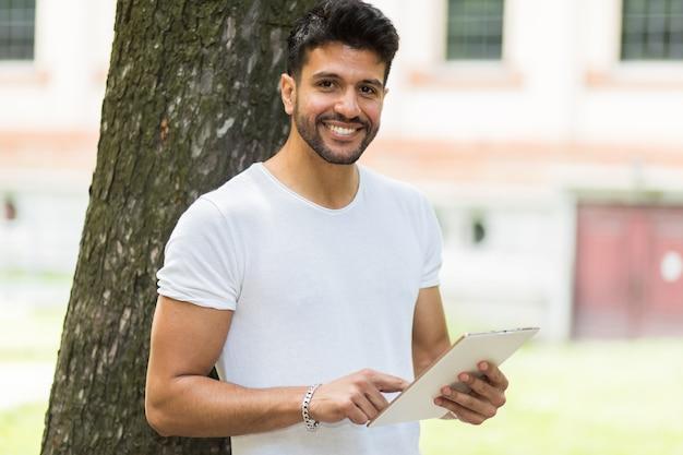 Junger kerl, der eine digitale tablette liegt gegen einen baum im park verwendet und die freiheit genießt