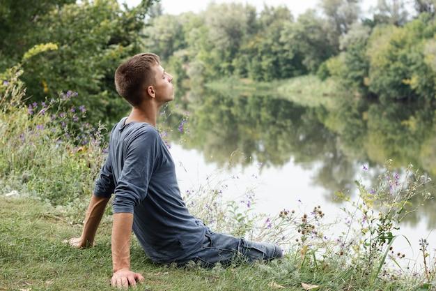 Junger kerl, der fern neben einem see schaut
