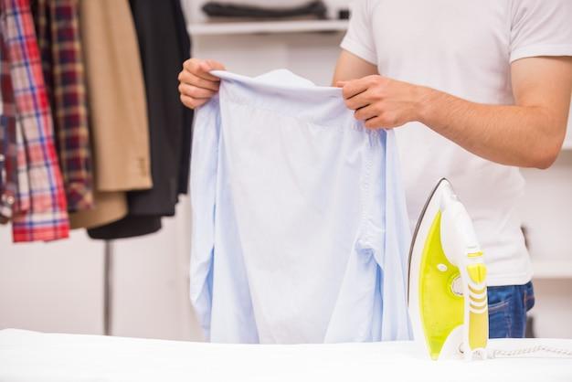 Junger kerl, der geht, sein hemd in der umkleidekabine zu bügeln.