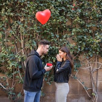 Junger kerl, der geschenkbox überraschter dame nahe fliegendem ballon in der form des herzens darstellt