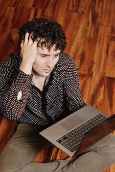 Junger kerl, der im internet nach anzeichen von krankheit sucht. cyberchondria
