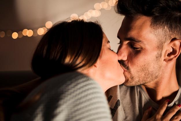 Junger kerl, der mit dame nahe feenlichtern küsst