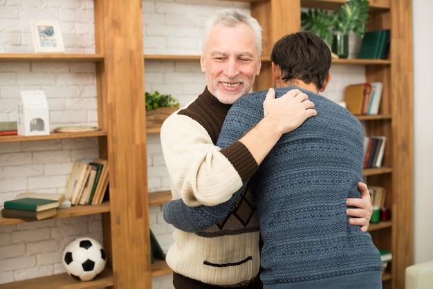 Junger kerl, der mit gealtertem lächelndem mann nahe bücherregalen umarmt