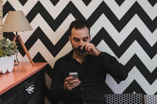 Junger kerl, der mit seinem handy an der bar simst und einen cappuccino isst.