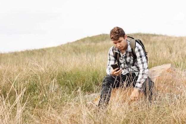 Junger kerl, der sein telefon in der wilden natur cheking ist