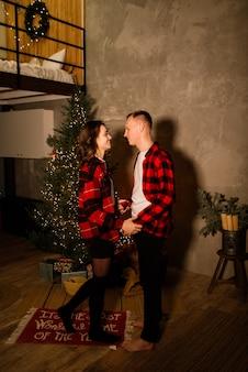 Junger kerl, der seine schöne freundin küsst, fühlt sich glücklich, während er zusammen winterferien feiert