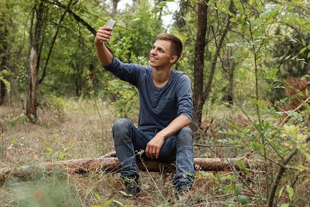 Junger kerl, der selfie im wald nimmt