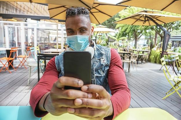 Junger kerl, der smartphone am restaurant benutzt