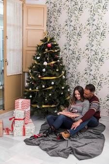 Junger kerl, der von der hinteren netten dame mit der geschenkbox umarmt, die nahe weihnachtsbaum sitzt