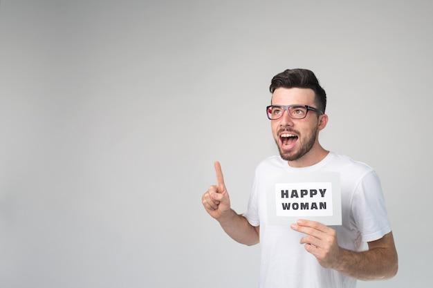 Junger kerl hält stück papier mit glücklichen frauenwörtern darauf. unterrichtet und zeigt mit dem finger nach oben. tragen sie ein weißes hemd und eine brille. lehrer oder mentor.