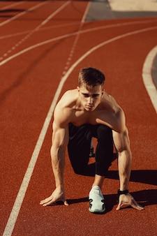 Junger kerl mit athletischem körper macht sich bereit zu laufen
