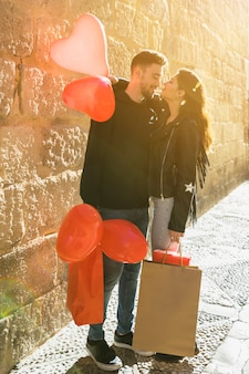 Junger kerl mit den paketen, die dame mit ballonen auf straße umarmen