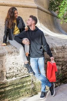 Junger kerl mit den paketen, die dame umarmt, die auf stein sitzt