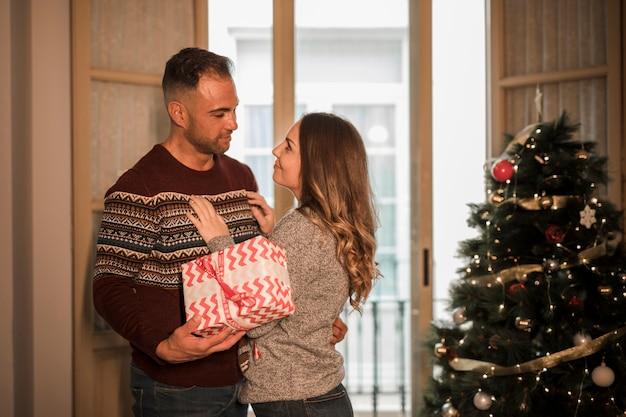 Junger kerl mit der geschenkbox, die nette dame nahe weihnachtsbaum umfasst