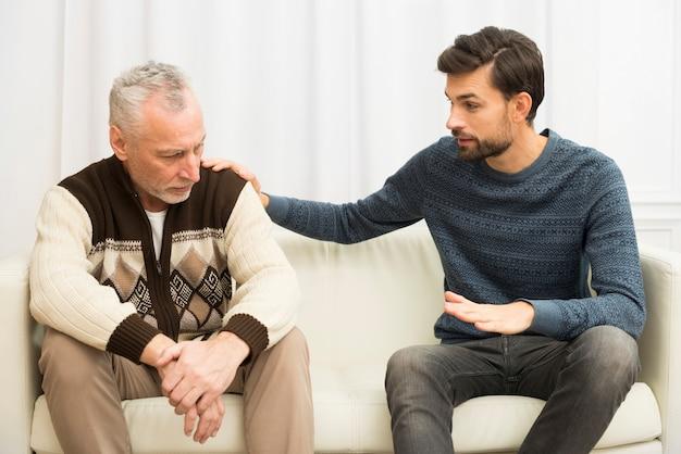 Junger kerl mit der hand auf schulter des gealterten traurigen mannes auf sofa