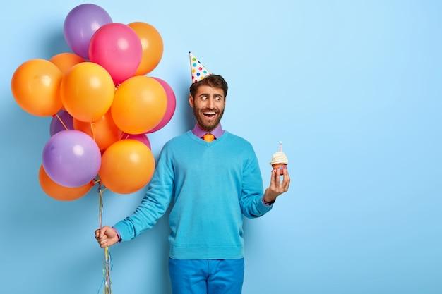 Junger kerl mit geburtstagshut und luftballons, die im blauen pullover aufwerfen