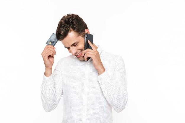 Junger kerl mit kurzen dunklen haaren, die auf smartphone sprechen und kreditkarte halten