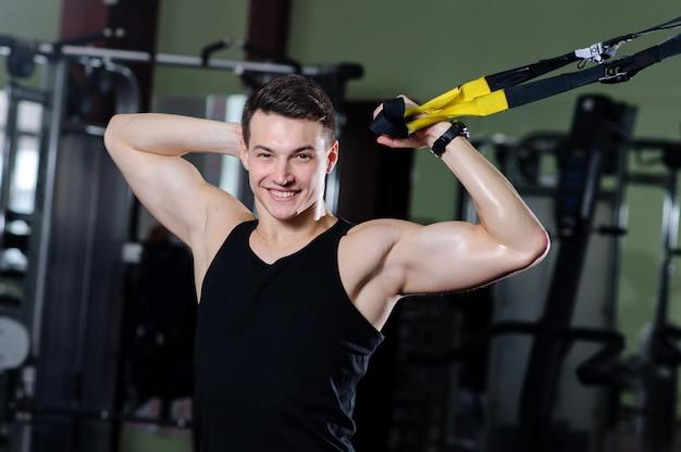 Junger kerl nimmt an einer sporthalle im trx teil
