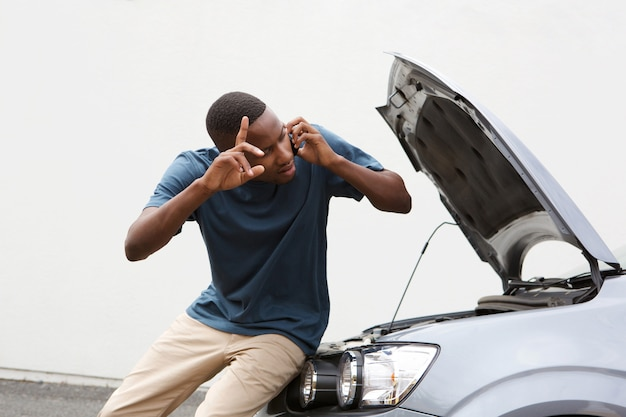Junger kerl ruft nach hilfe mit kaputten auto