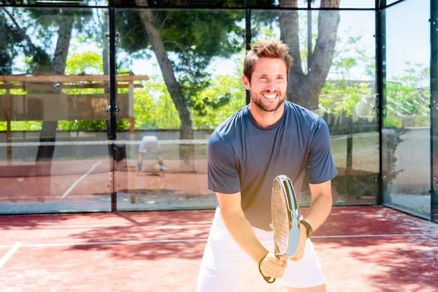 Junger kerl spielt padel-tennis im sommersportplatz im freien und wird fit