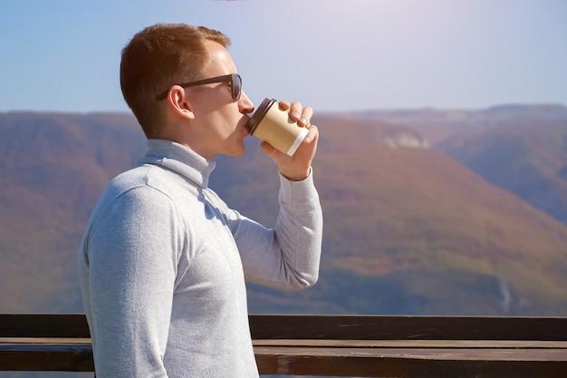Junger kerl trinkt kaffee gegen berge an einem klaren tag, sonnenlicht
