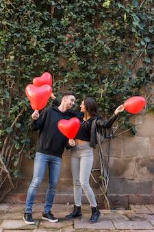 Junger kerl und lächelnde dame, die ballone in der form von herzen hält