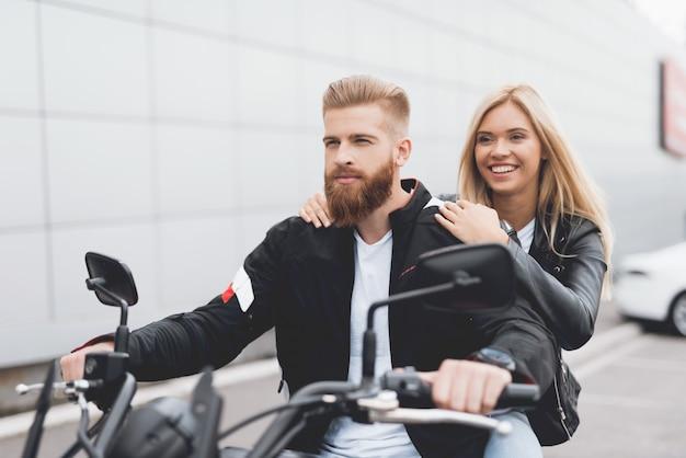 Junger kerl und mädchen, die auf einem modernen elektrischen motorrad sitzt.