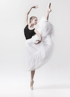 Junger klassischer tänzer, der auf weiß tanzt. ballerina-projekt.