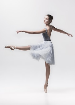 Junger klassischer tänzer, der auf weiß tanzt
