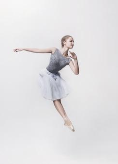 Junger klassischer tänzer, der auf weißem hintergrund tanzt. ballerina-projekt.