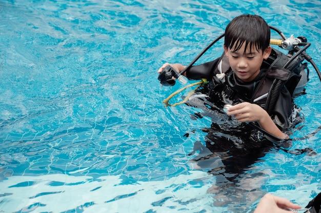 Junger kleiner asiatischer jungensporttaucher, der manometer überprüft und regulato hält
