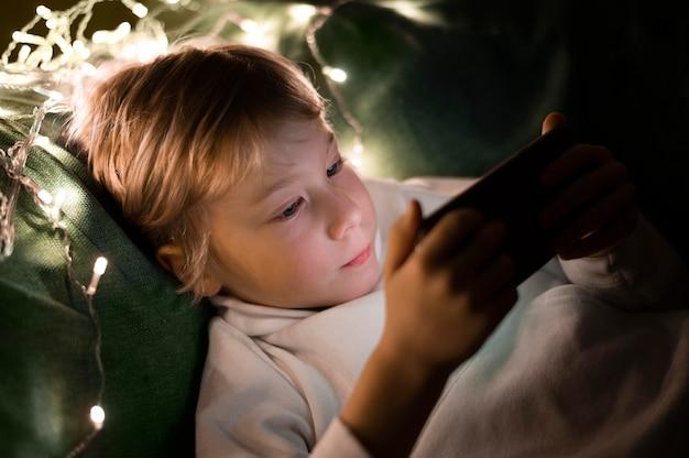 Junger kleiner junge, der smartphone im bett in der nacht benutzt