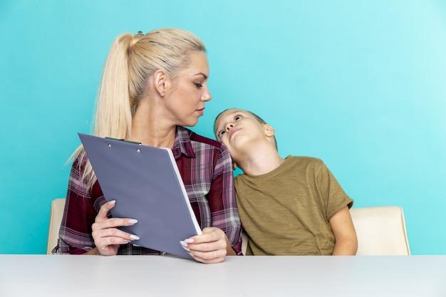 Junger kleiner schüler, der hausaufgaben mit mutter macht, zusammenarbeit in der familie, elternschaft.