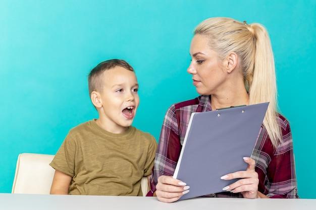 Junger kleiner schüler, der hausaufgaben mit mutter macht, zusammenarbeit in der familie