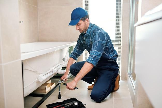 Junger klempner oder techniker in der arbeitskleidung, der detail für badewanneninstallation vorbereitet, während er auf kniebeugen sitzt