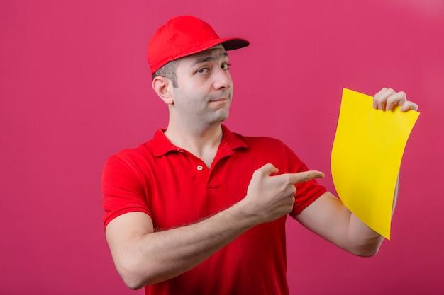 Junger klug aussehender lieferbote im roten poloshirt und in der kappe, die finger auf gelbes blatt papier mit sicherem blick über lokalisiertem rosa hintergrund zeigen