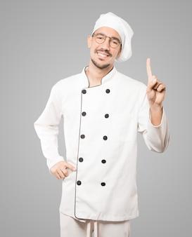 Junger koch, der eine geste nummer eins macht