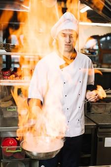 Junger koch, der in der hand brennende wanne hält