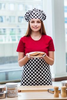 Junger koch, der plätzchen in der küche zubereitet