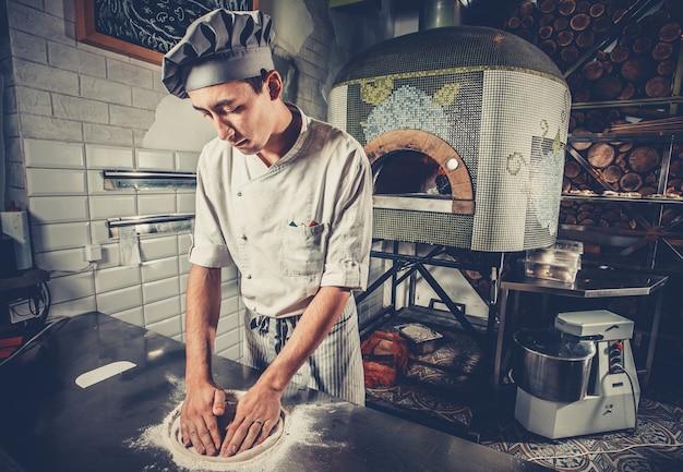 Junger koch, der teig im restaurant vorbereitet
