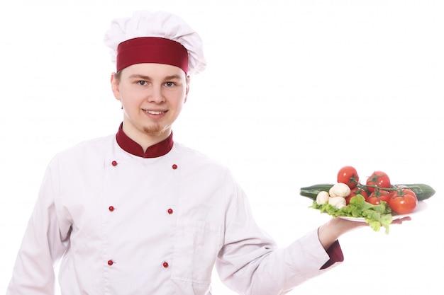 Junger koch, der teller mit gemüse hält