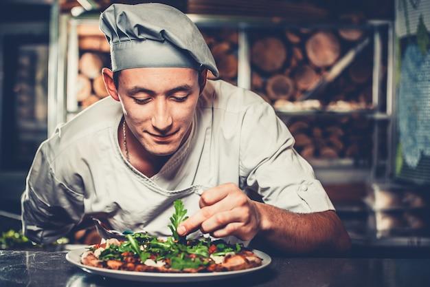 Junger koch, der traditionelle italienische pizza vorbereitet
