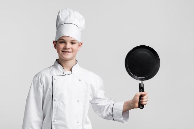Junger koch der vorderansicht, der kochpfanne hält