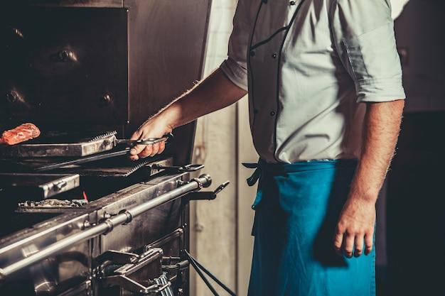 Junger koch in der weißen uniform, die fleisch kocht