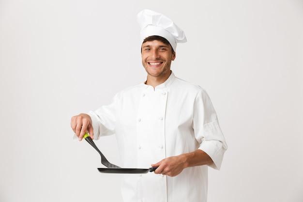 Junger koch mann steht isoliert auf weißer wand mit bratpfanne kochen
