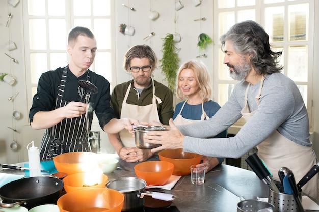 Junger koch oder trainer in schürze, der kochwerkzeuge hält und mit wasser über dem tisch schwenkt, während ein älterer mann ihm unter anderen lernenden hilft