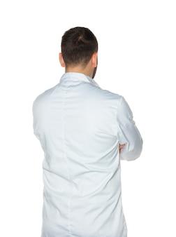 Junger koch von hinten in der weißen uniform lokalisiert auf weißer wand.