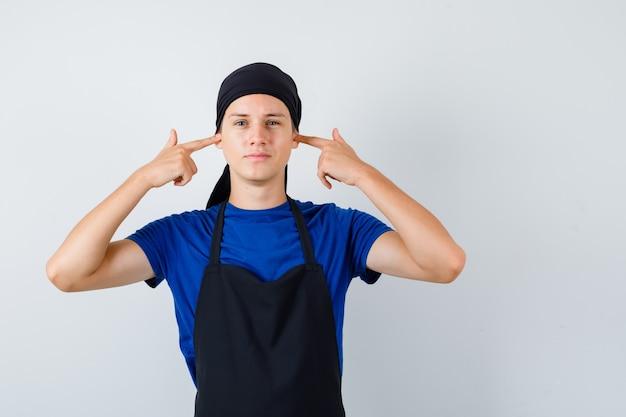 Junger kochmann im t-shirt, schürze, die ohren mit den fingern verstopft und genervt aussieht, vorderansicht.